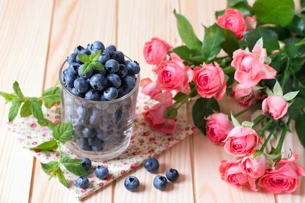 Bleuets frais dans un verre et fleurs sur une table en bois