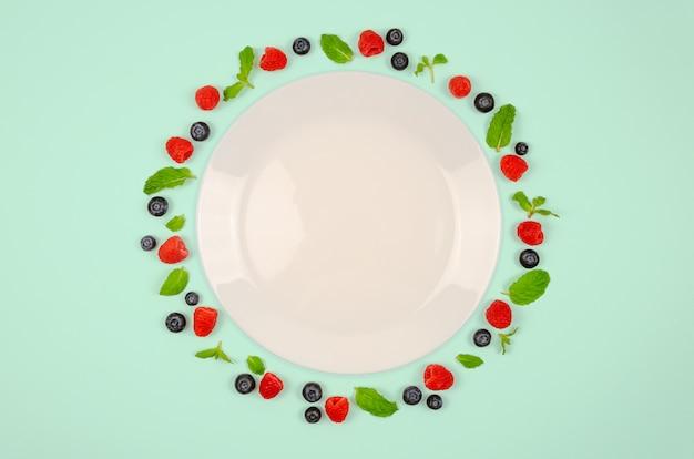 Bleuets frais, framboises et feuille de menthe avec plaque blanche