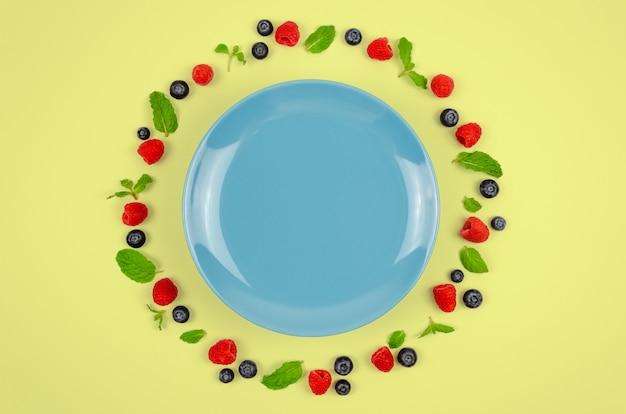 Bleuets frais, framboises et feuille de menthe avec plaque bleue.