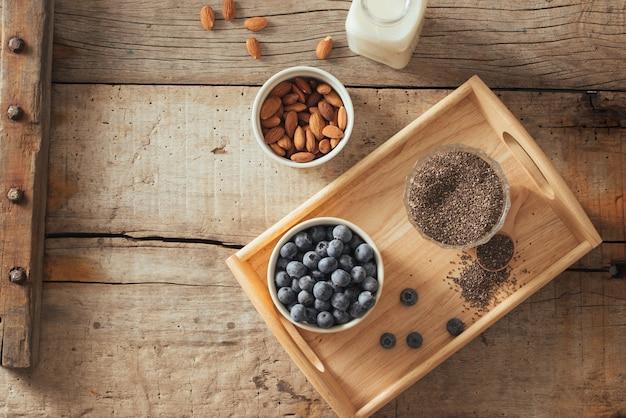Bleuets frais, graines d'amande et de chia avec du lait sur planche de bois. concept de petit-déjeuner sain idéal.
