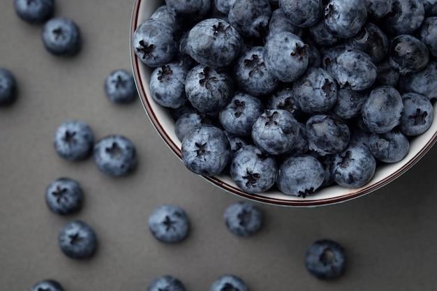 Bleuets frais sélectionnés dans un bol sur une table gris foncé