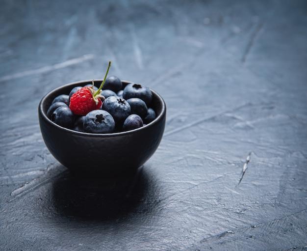 Bleuets frais et sucrés dans un bol noir avec framboise sur noir.