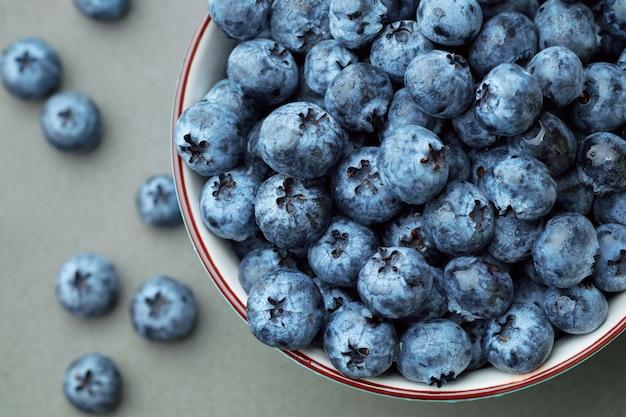 Bleuets sélectionnés frais dans un bol sur table gris foncé