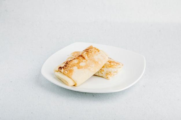 Blinchik apéritif russe, crêpes à l'intérieur de la plaque blanche.