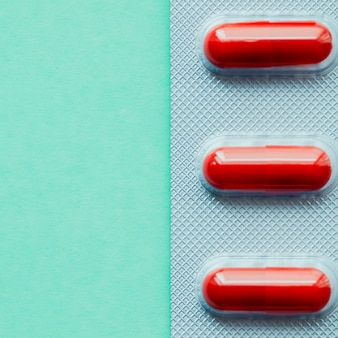 Blister comprimés rouges vives sur fond vert.