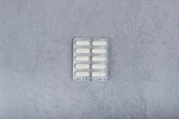Un blister avec des pilules blanches sur une surface grise