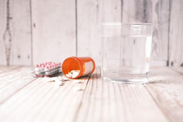 Blister de pilules médicales et verre d'eau sur la table