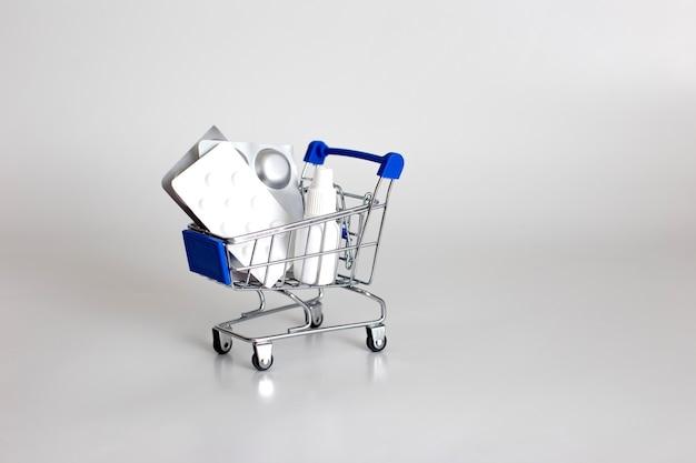 Blisters blancs et argentés de pilules et de gouttes dans un chariot de supermarché sur blanc