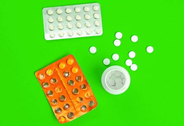 Blisters et une bouteille de pilules sur fond vert.