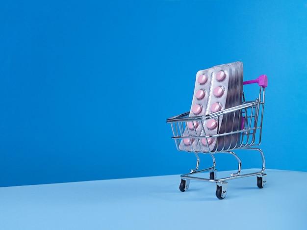 Blisters de comprimés roses en chariot de supermarché sur bleu avec skyline tendance inclinée