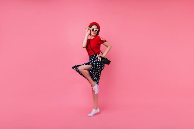 Blithesome fille mince dans la danse du béret français. belle dame aux cheveux courts en jupe noire sautant sur un mur rose.
