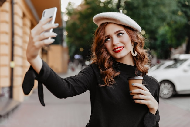 Blithesome fille rousse tenant une tasse de café et posant en plein air. jeune femme française insouciante faisant selfie dans la rue.