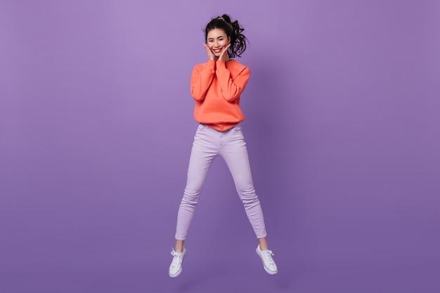 Blithesome jeune femme asiatique sautant et regardant la caméra. superbe femme japonaise dansant sur fond violet.