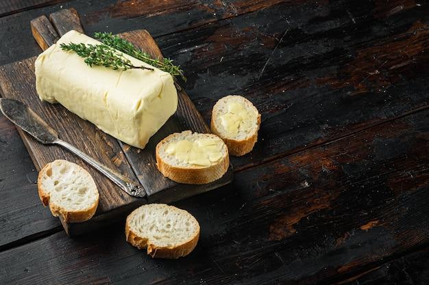 Bloc de beurre frais, sur le vieux fond de table en bois foncé avec copie espace pour le texte
