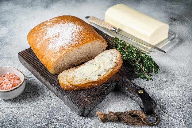 Bloc de beurre et tranches de pain grillé sur une planche de bois avec des herbes