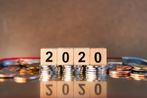 Bloc de bois année 2020 avec pile de pièces utilisant comme concept bancaire et financier d'entreprise