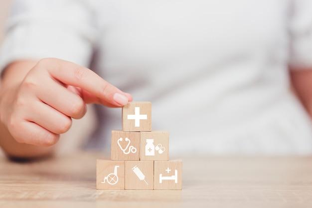 Bloc de bois d'assurance maladie empiler avec l'icône de soins de santé médical.