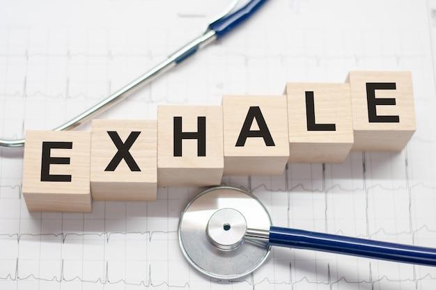 Bloc en bois forment le mot exhale avec stéthoscope sur le bureau du médecin. concept médical. soins de santé conceptuels pour les hôpitaux, les cliniques et les entreprises médicales