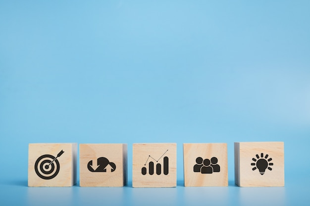 Bloc de bois avec icône stratégie commerciale et plan d'action. objectif et objectif, concept de réussite et d'objectif commercial, gestion de projet, développement de stratégie d'entreprise. espace de copie.