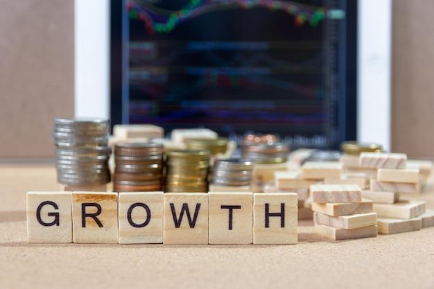 Bloc de bois mot croissance sur les tablettes avec pièce en baisse tendance, concept d'entreprise.