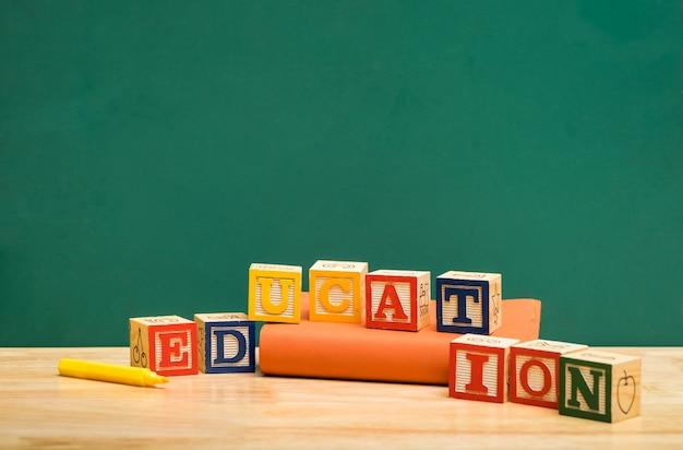 Bloc de bois mot éducation coloré sur le livre avec un stylo sur la table en bois avec tableau noir vert