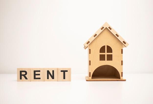 Bloc en bois avec mot de location et modèle de maison sur la maison et les finances,