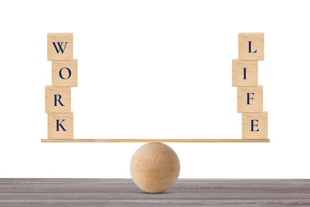 Bloc de bois avec des mots travail et vie sur balançoire en bois en équilibre sur un bureau en bois et mur blanc
