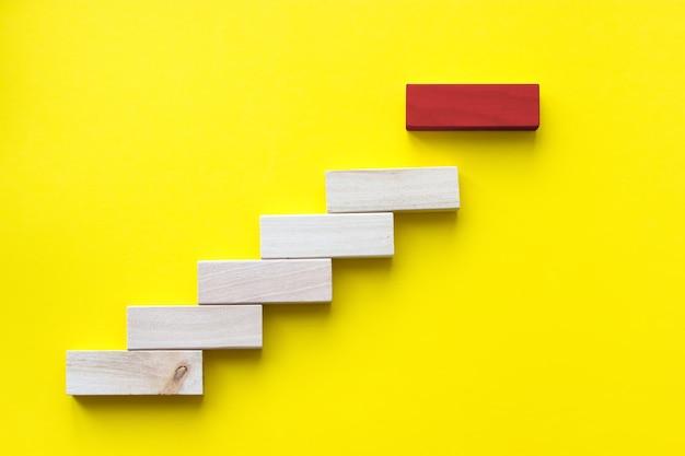 Bloc de bois rouge sur jaune stratégie de leader de solution de gestion des risques de planification d'entreprise différente