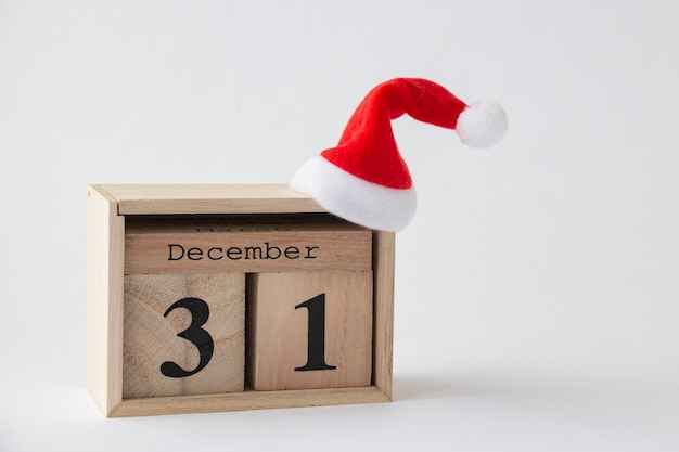 Un bloc de calendrier blanc avec un capuchon rouge a une date de 31 et le mois de décembre sur fond blanc