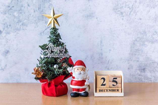 Bloc calendrier date du 25 décembre calendrier et décoration de noël - père noël, arbre et cadeau sur table en bois. concept de noël et bonne année