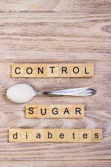 Bloc de contrôle du diabète, lettres en bois et tas de sucre sur une cuillère