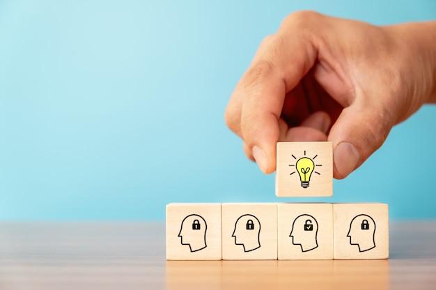 Bloc de cube en bois cueilli à la main avec l'icône de l'ampoule sur un bloc de bois avec l'icône de déverrouillage et la tête