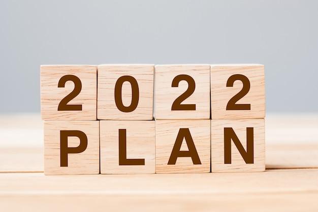 Bloc de cube plan 2022 sur fond de table. résolution, objectif, révision, modification, concepts de vacances de début et de nouvel an