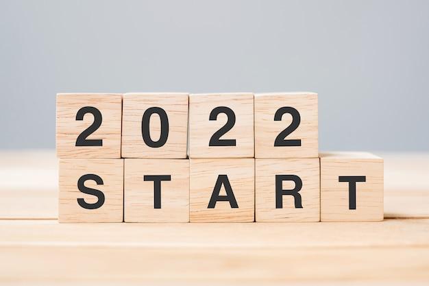 Bloc de cube start 2022 sur fond de table. résolution, planification, révision, changement et concepts de vacances du nouvel an