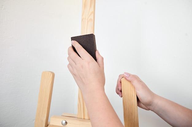 Bloc éponge de broyage à la main. personne polit la surface d'un chevalet en bois