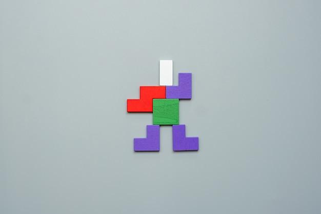 Bloc de forme homme de pièce de puzzle en bois coloré sur fond gris