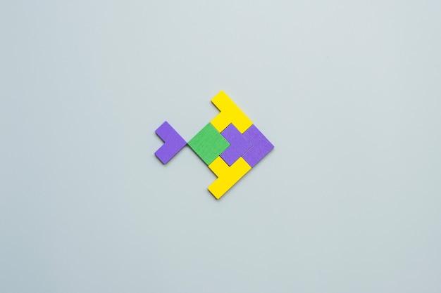 Bloc de forme de poisson de pièce de puzzle en bois coloré sur fond gris.