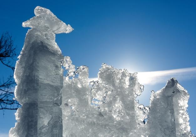 Bloc de glace de fonte avec soleil derrière sur fond de ciel bleu.