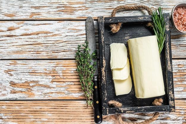 Bloc de margarine au beurre dans un plateau en bois avec des herbes. fond en bois blanc. vue de dessus. espace de copie.