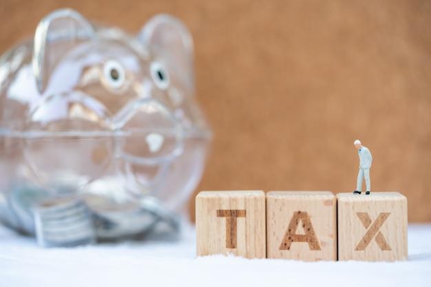 Bloc de mot tax avec tirelire. revenus, dépenses, impôts et données financières.