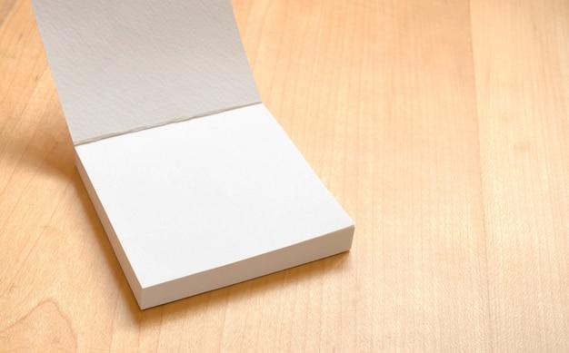Bloc-notes blanc blanc sur la table en bois, modèle maquette pour ajouter votre texte