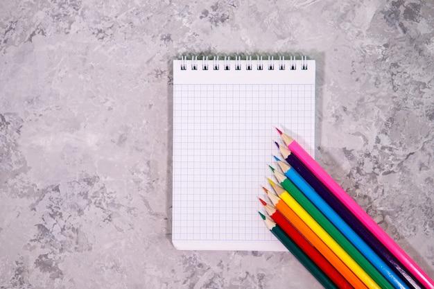 Bloc-notes blanc avec des crayons de couleur