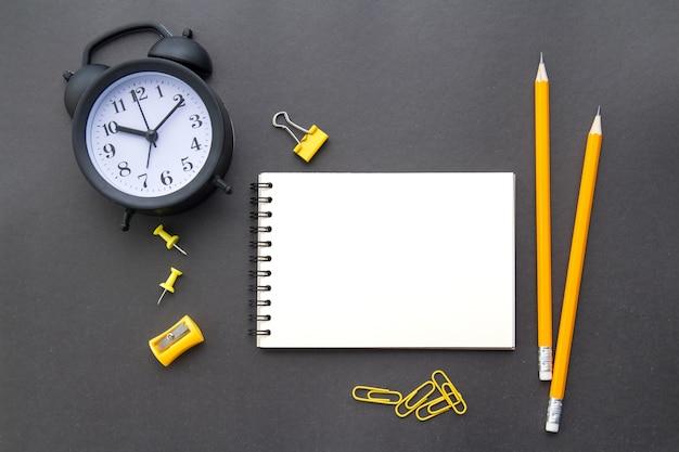Un bloc-notes blanc, crayons jaunes, articles de papeterie et un réveil noir sur fond noir, à plat