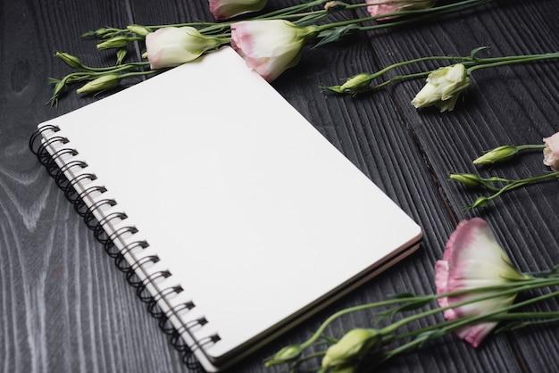 Bloc-notes blanc en spirale avec des fleurs d'eustoma pourpre sur le bureau en bois