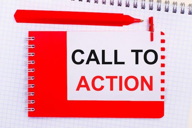 Sur un bloc-notes blanc, un stylo rouge, un bloc-notes rouge et une feuille de papier blanche avec le texte appel à l'action