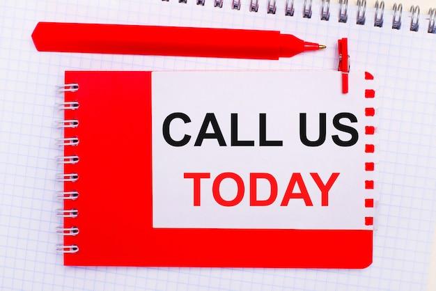 Sur un bloc-notes blanc, un stylo rouge, un bloc-notes rouge et une feuille de papier blanche avec le texte appelez-nous aujourd'hui