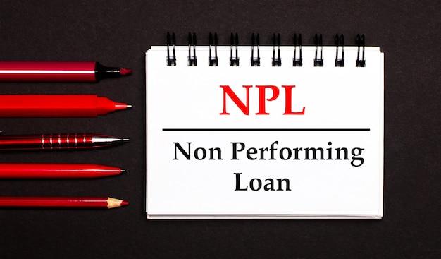 Un bloc-notes blanc avec le texte prêt non performant npl, écrit sur un bloc-notes blanc à côté de stylos rouges, crayons et marqueurs sur une surface noire
