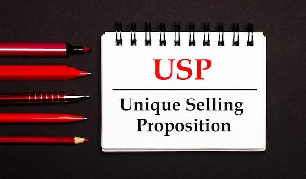 Un bloc-notes blanc avec le texte usp unique selling proposition, écrit sur un bloc-notes blanc à côté de stylos, crayons et marqueurs rouges sur fond noir.