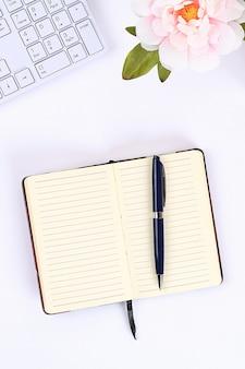 Un bloc-notes blanc vierge sur un bureau blanc