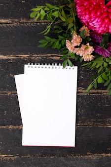 Bloc-notes avec un bouquet de fleurs sur un bois vintage foncé